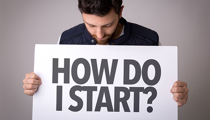 Young man holding 'How Do I Start' Board
